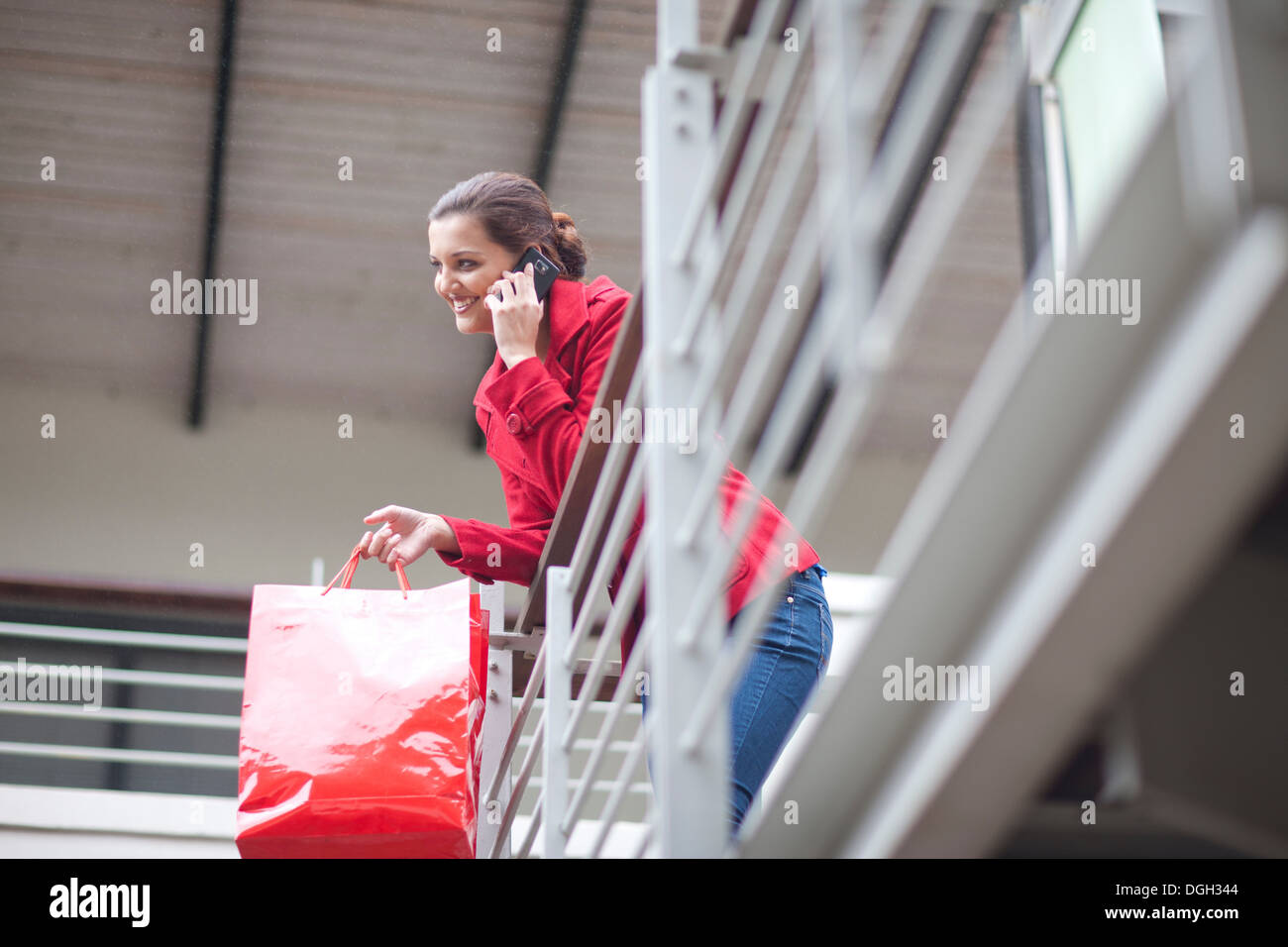 Young woman on cellphone in shopping mall - Stock Image