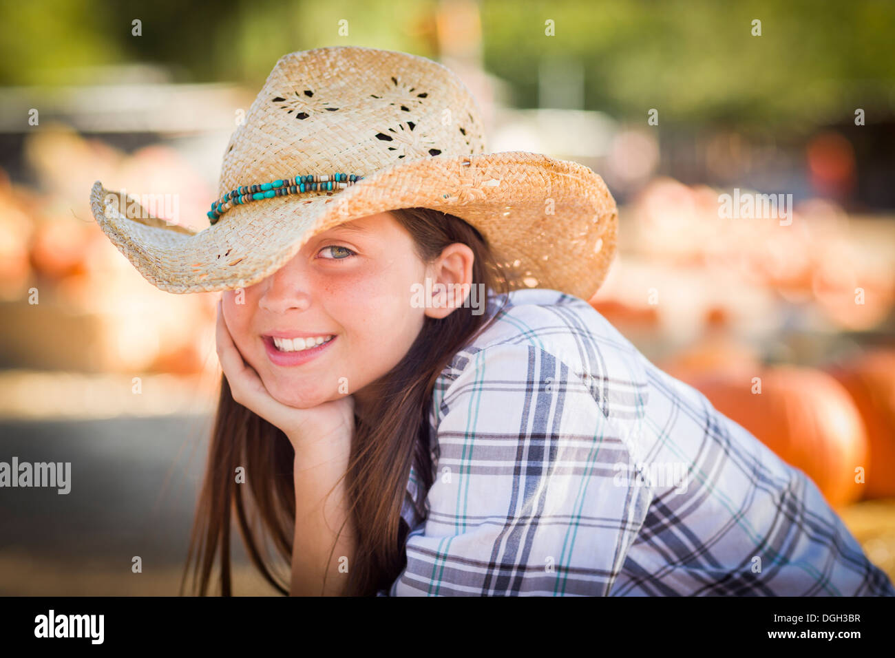 Preteen Girl Wearing Cowboy Hat Portrait at the Pumpkin Patch in a Rustic Setting. Stock Photo