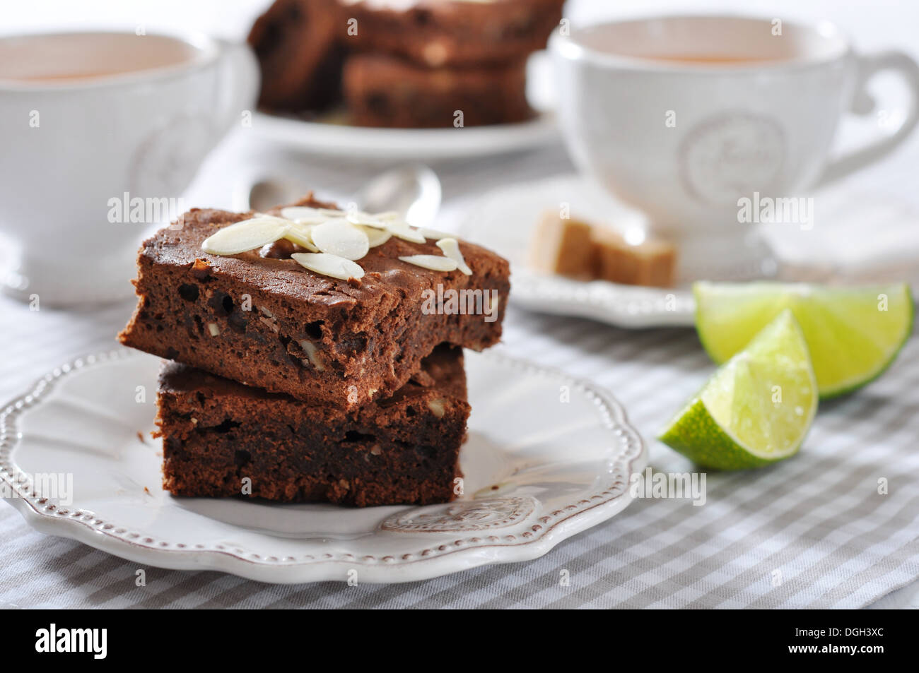 Brownie cake with almond flakes and cup of tea closeup - Stock Image