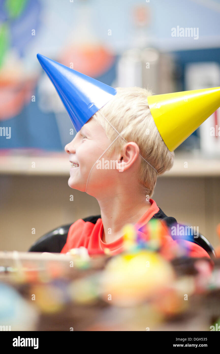 Boy at birthday party wearing two party hats - Stock Image