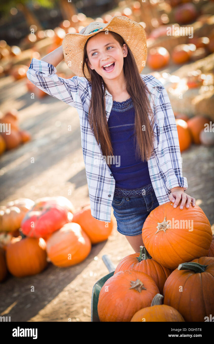 788c53c9ac8 Preteen Girl Wearing Cowboy Hat Playing with a Wheelbarrow at the Pumpkin  Patch in a Rustic Country Setting.