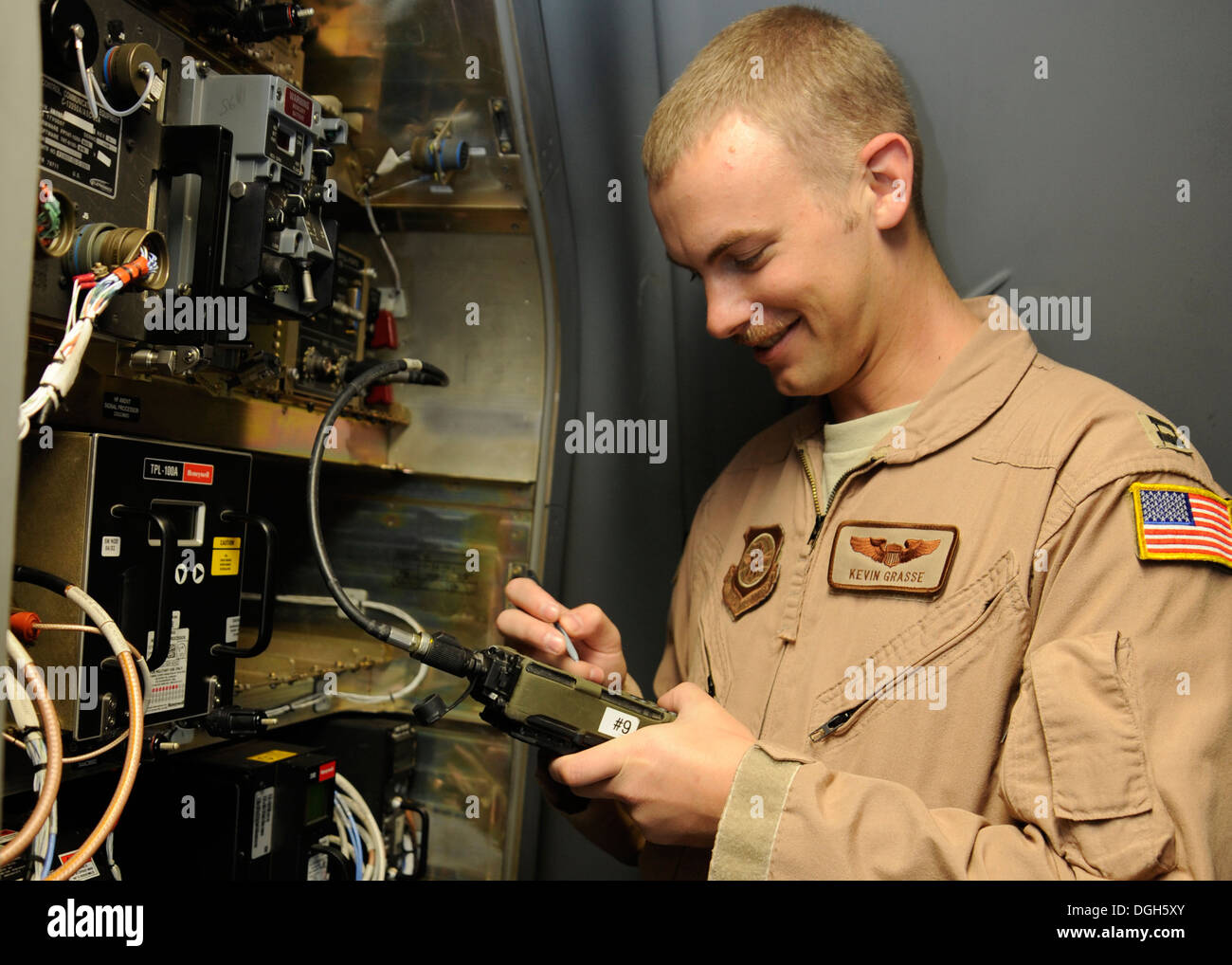 Capt. Kevin Grasse loads data into avionics equipment prior to a C-17 Globemaster III mission at the 379th Air Expeditionary Wing in Southwest Asia, Oct. 13, 2013. Capable of strategic delivery of troops and a broad range of cargo, the C-17 and its aircre - Stock Image