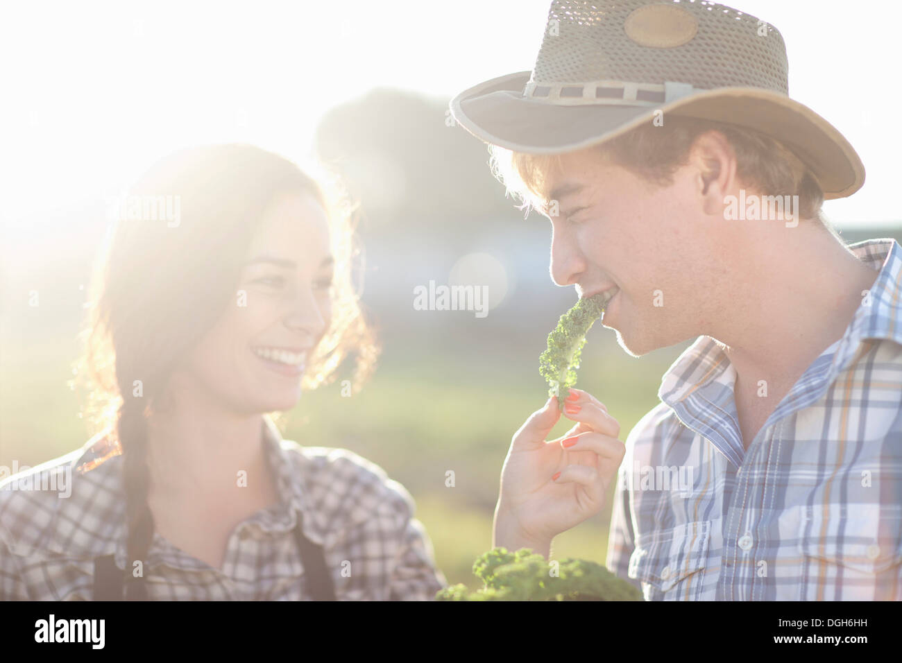 Young couple trying vegetables on farm - Stock Image