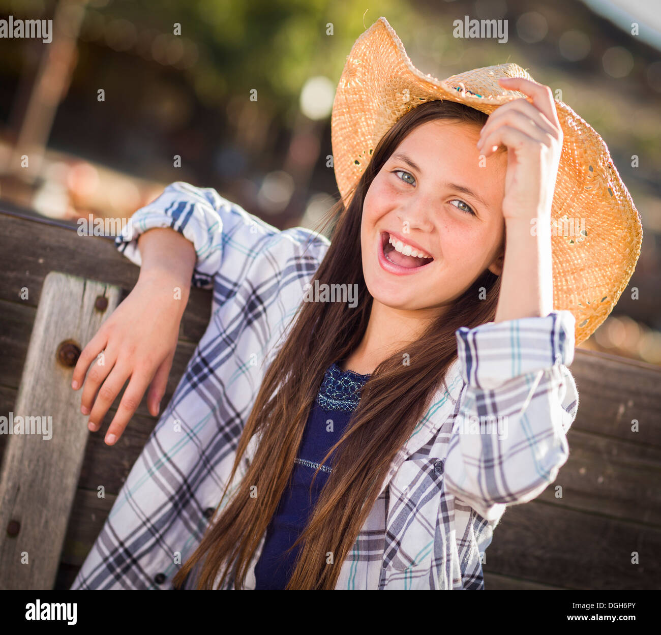 53fe6ef50ce Preteen Girl Wearing Cowboy Hat Portrait at the Pumpkin Patch in a Rustic  Setting.
