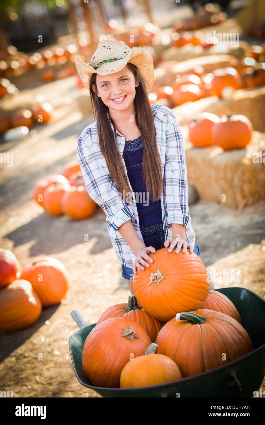 Preteen Girl Wearing Cowboy Hat Playing with a Wheelbarrow at the Pumpkin Patch in a Rustic Country Setting. Stock Photo