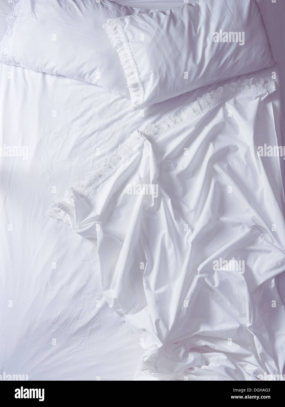 Empty unmade bed with ruffled white sheets in morning light, high angle view. - Stock Image