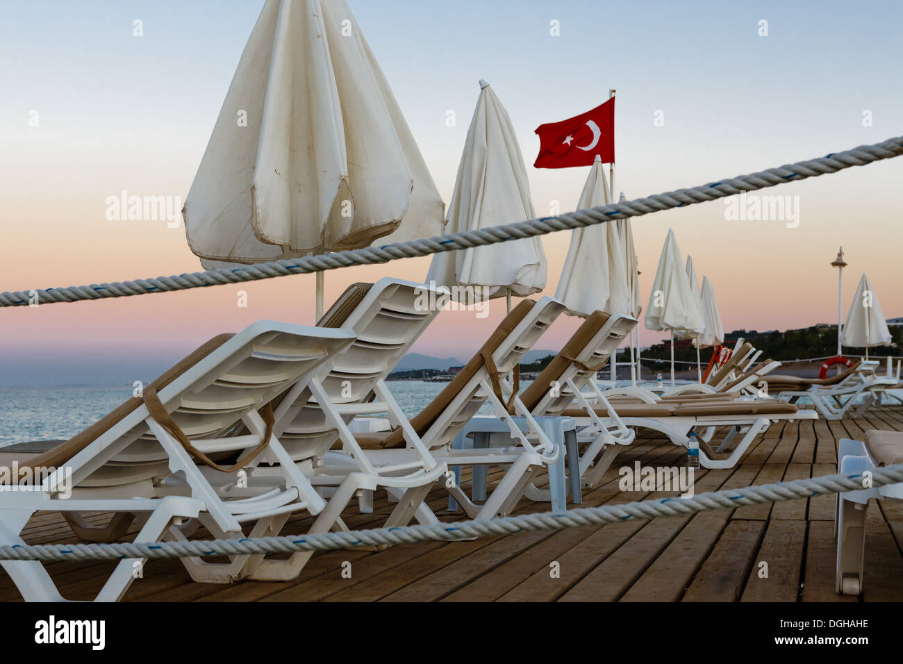 Chaise lounges and sun-protection umbrellas on a wooden pier in Turkish resort on a beach of Mediterranean Sea - Stock Image