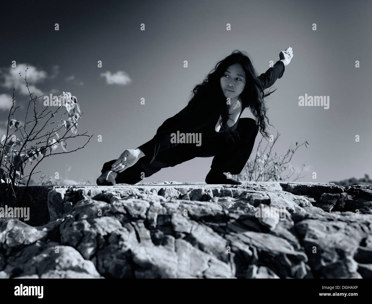Artistic dramatic portrait of a young asian woman martial artist practicing Kung Fu in the nature under blue sky. Stock Photo