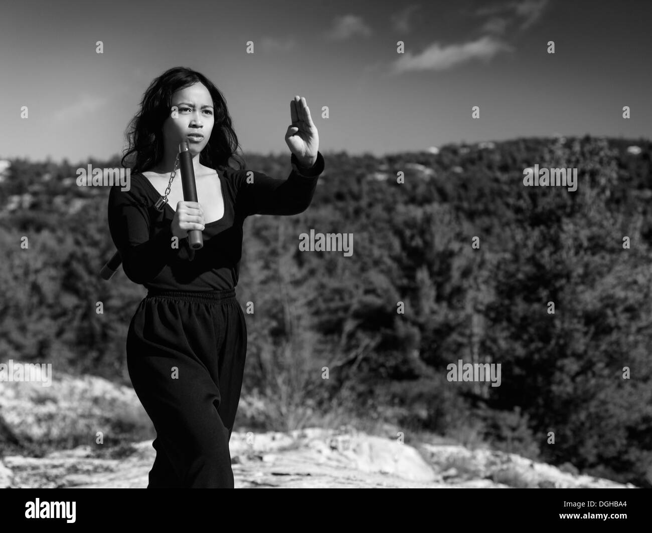 Dramatic black and white portrait of a young asian woman martial artis practicing nunchaku in the nature. Ontario, Stock Photo