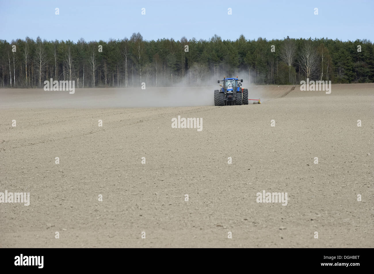 New Holland TM150 tractor, drilling in field with wind blown dust