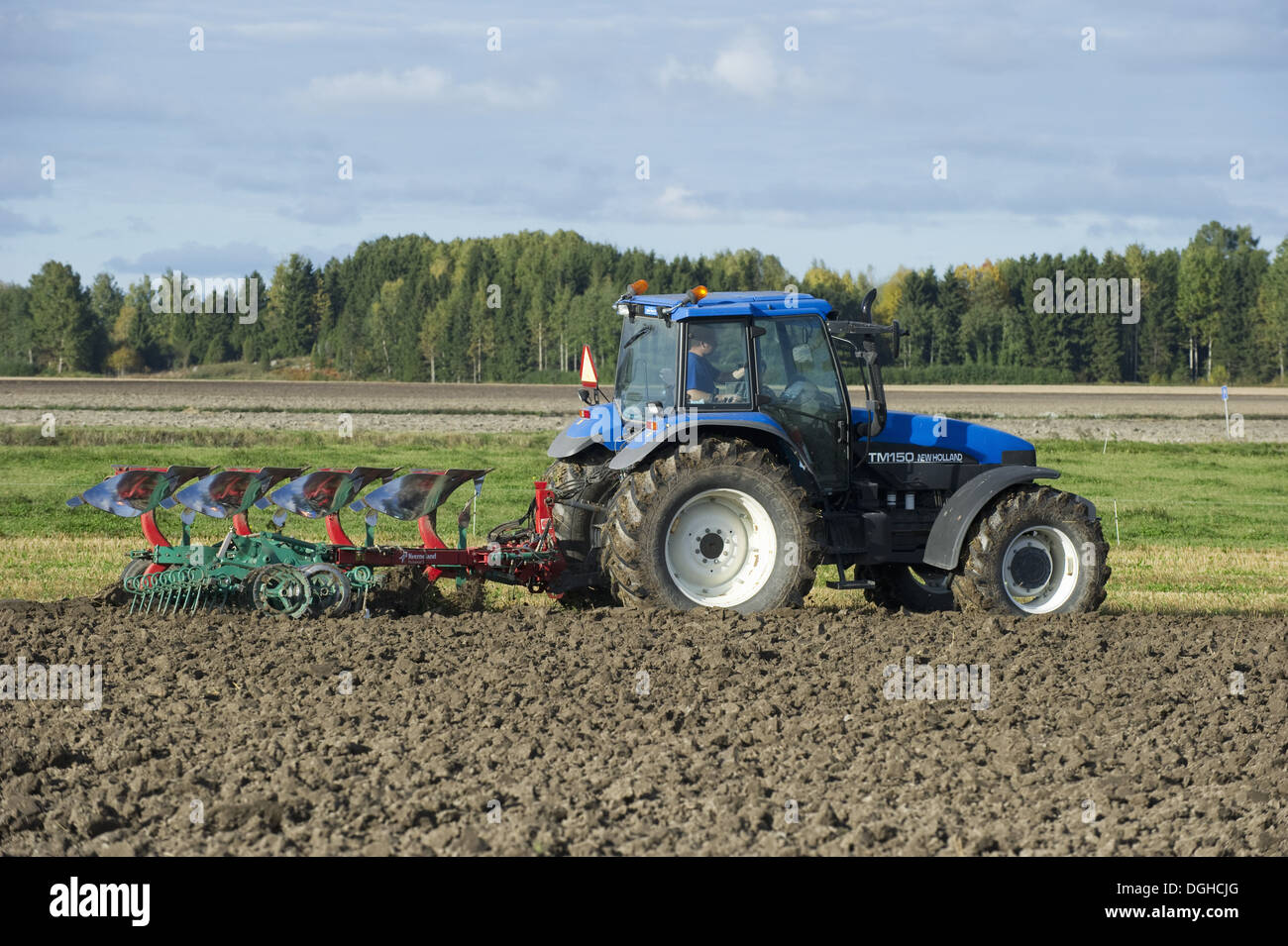 New Holland TM150 tractor with reversible plough and harrow Stock