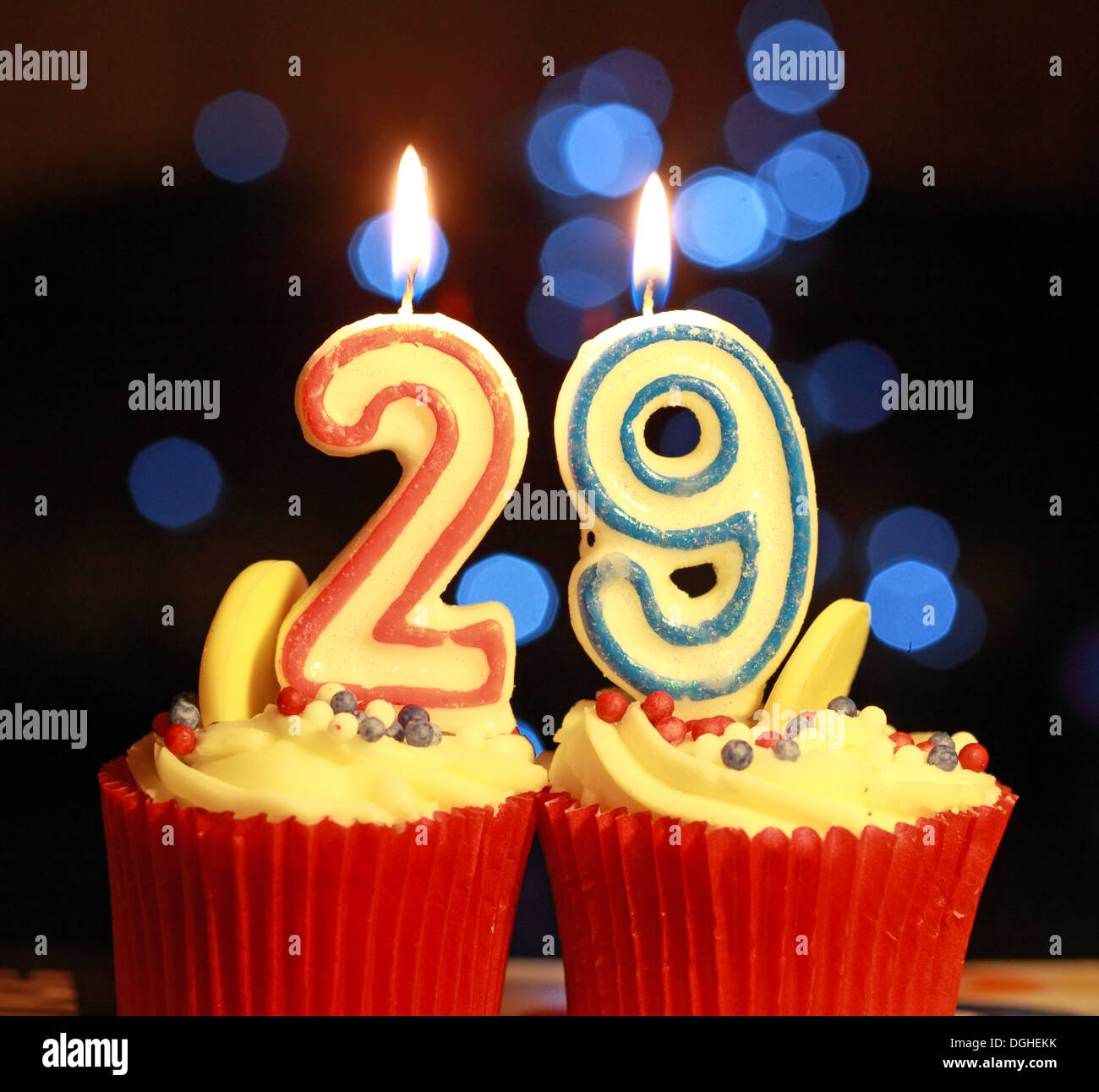 TwentyNine the number 29 as burning candles , on iced muffin - Stock Image