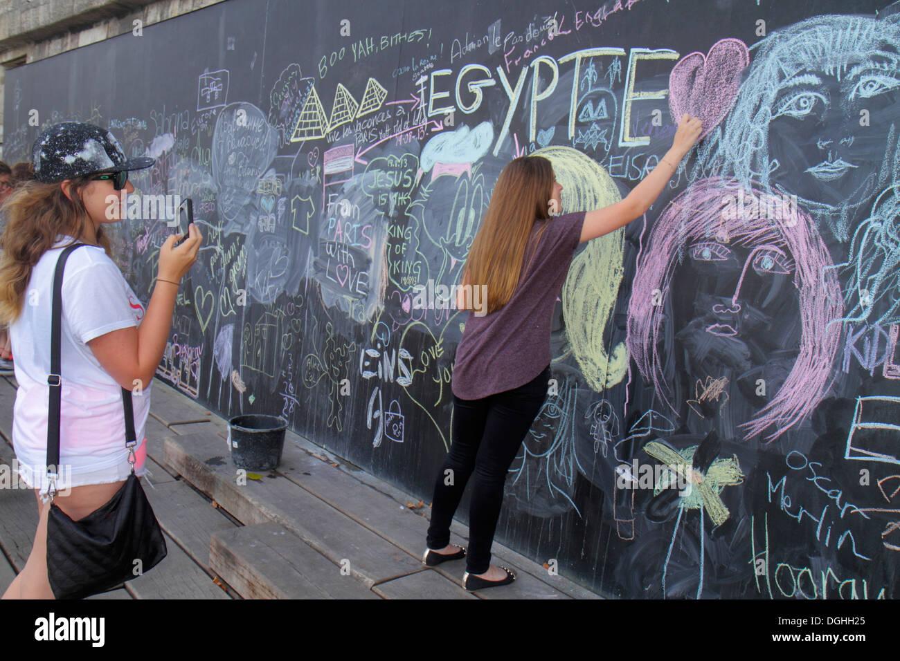 Paris France Europe French Seine River La Rive Gauche Left Bank Berges de Seine teen girl friends drawing giant chalkboard commu - Stock Image