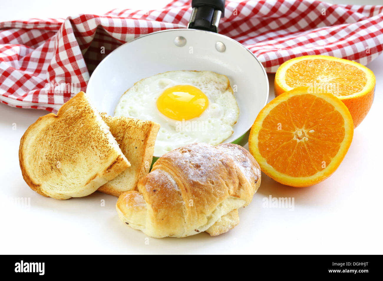 Continental breakfast - croissant, fried egg, toast and oranges - Stock Image