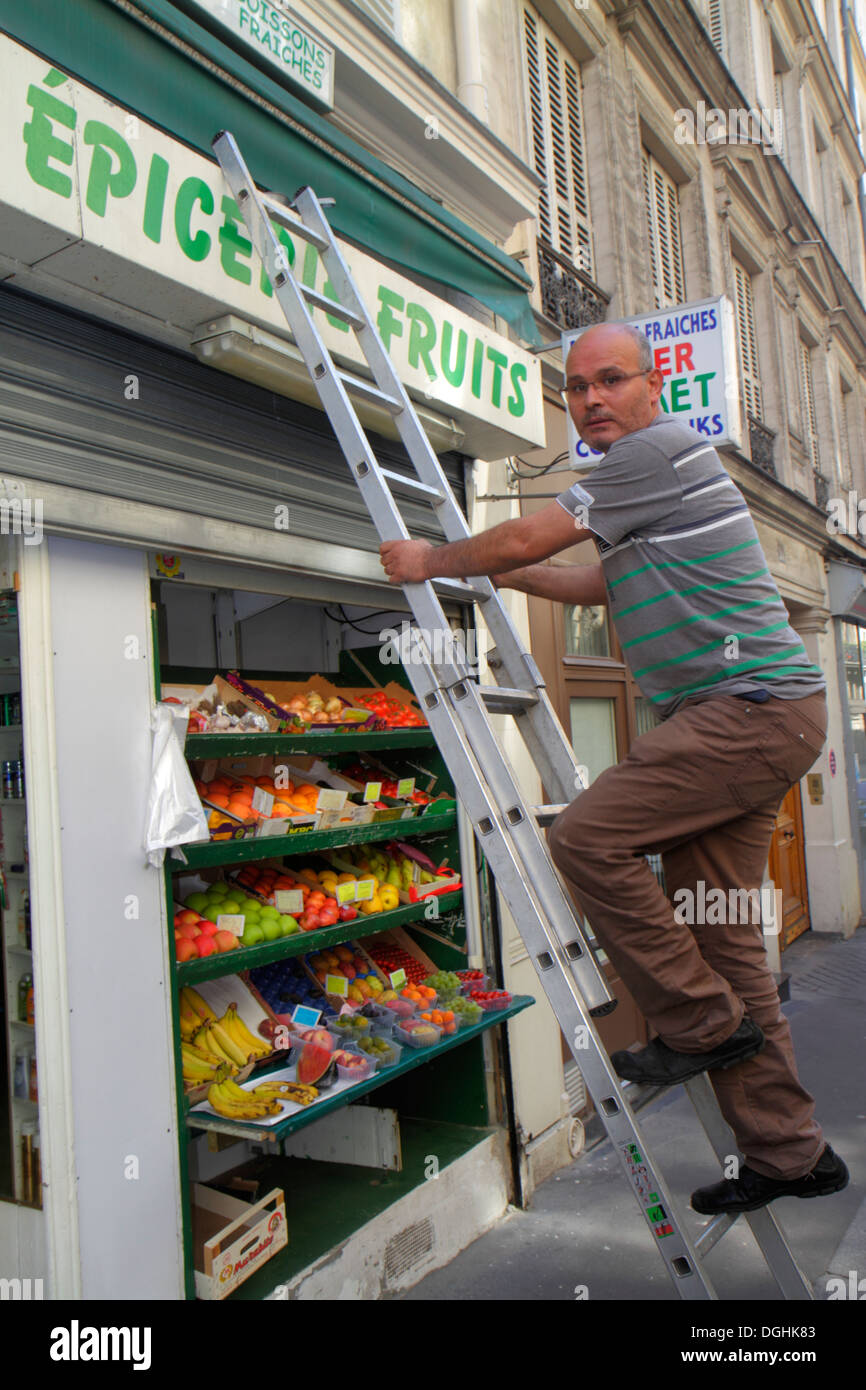 Paris France Europe French 9th arrondissement Rue Jean-Baptiste Pigalle man produce stand grocery store manager employee ladder - Stock Image
