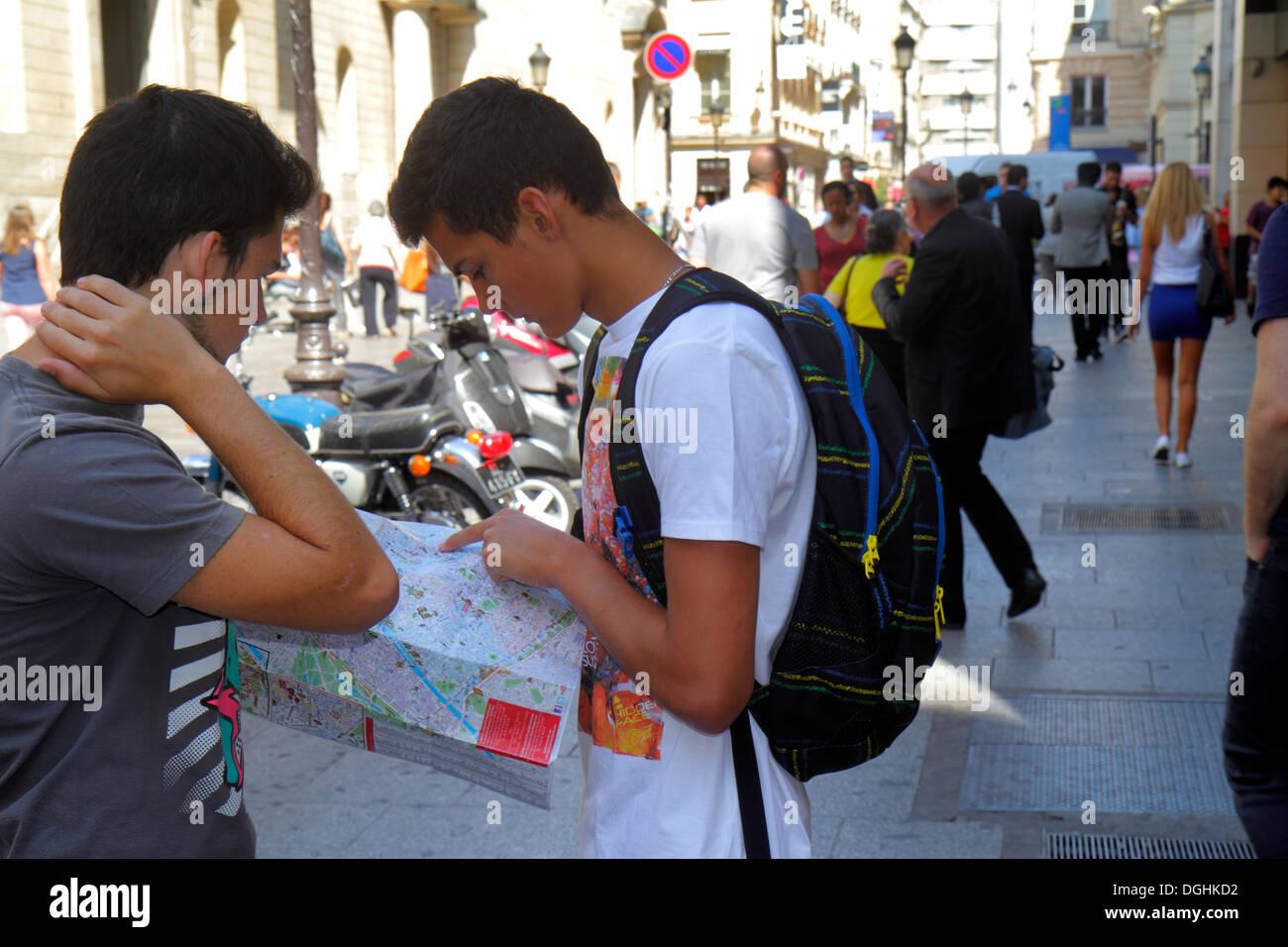 Paris France Europe French 9th arrondissement Boulevard Haussmann teen boy friends street map looking at - Stock Image