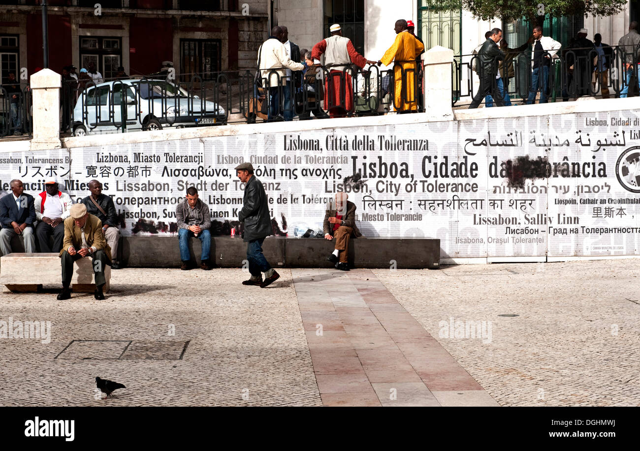People in a central square, calls for tolerance on a wall behind, Portugal, Europe - Stock Image