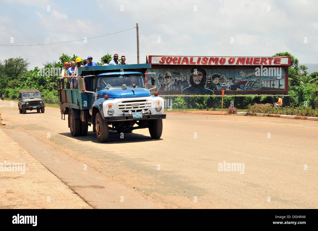 Truck with workers in front of socialist propaganda, Socialismo o muerte, socialism or death, in Moa, Cuba, Caribbean - Stock Image