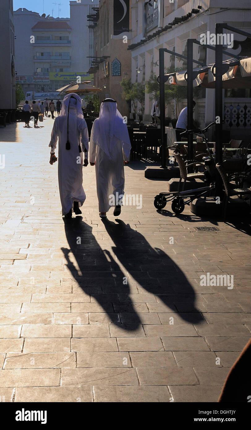 Qatari nationals wearing traditional white Thobe, Souk Waqif, Doha, Qatar Stock Photo