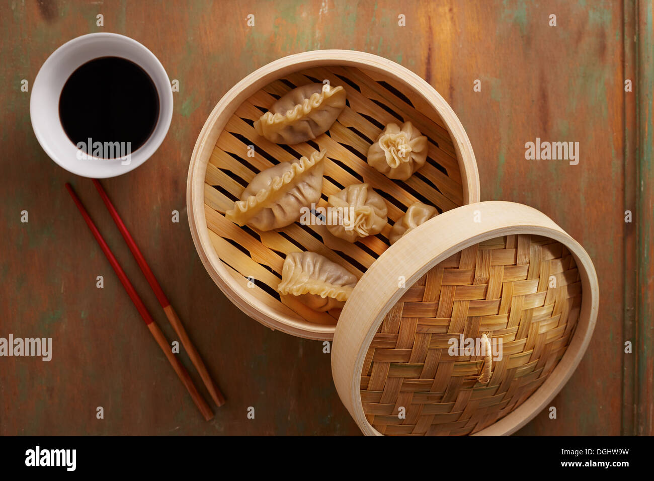 Homemade dim-sum asian dumplings on a traditional bamboo steamer - Stock Image