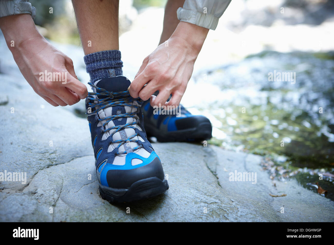 a man tying shoe laces in the woods Stock Photo