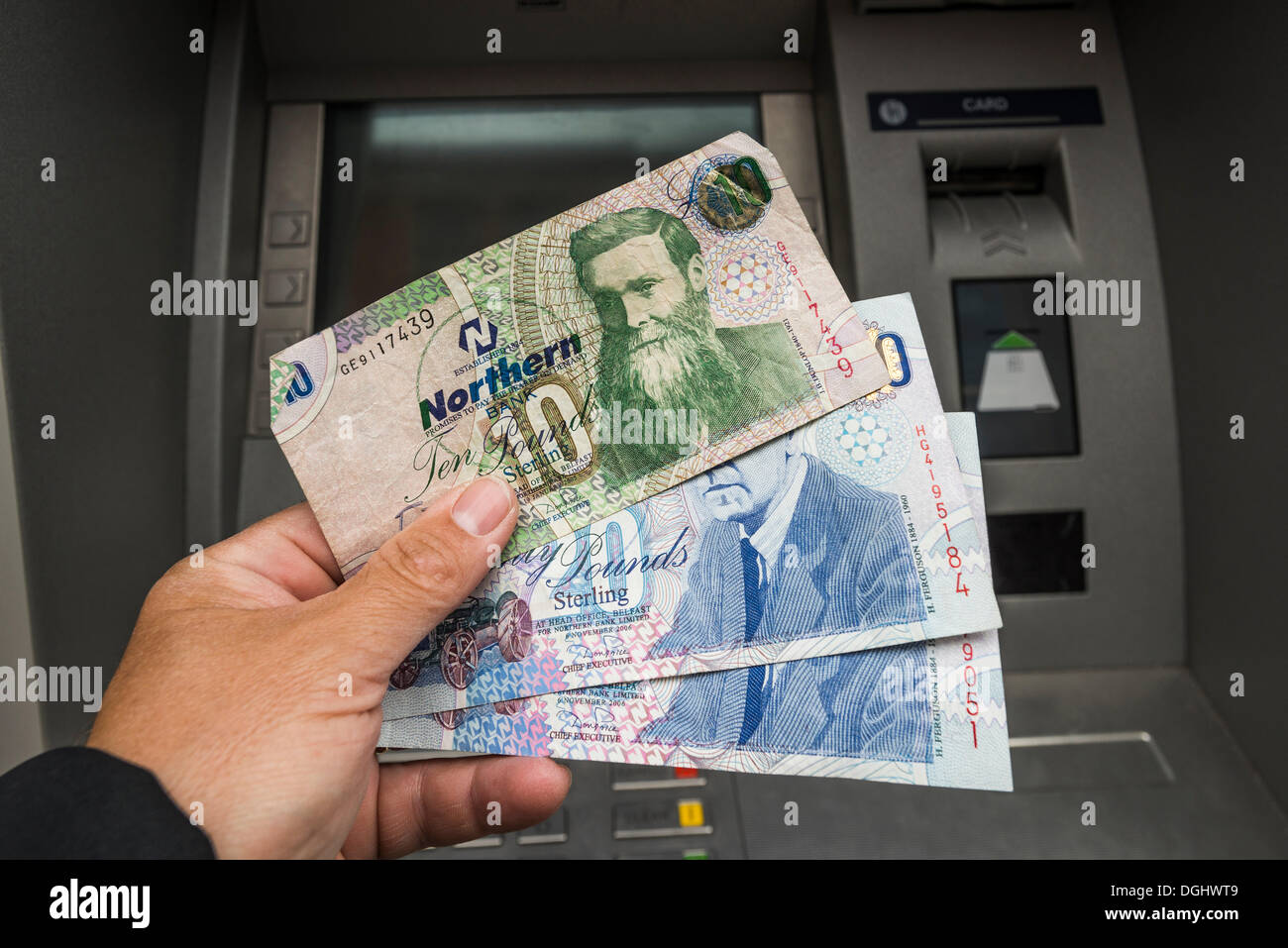 Northern Ireland 10 and 20 pound notes held in a hand in front of an ATM, Northern Ireland, United Kingdom - Stock Image
