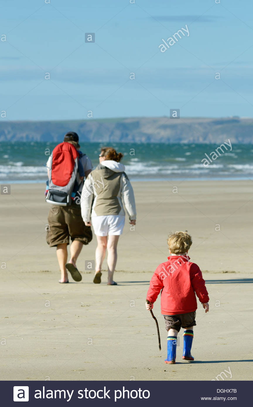 A man with a child in a carrier and woman walking on the beach at Little Haven with their little boy walking behind. - Stock Image