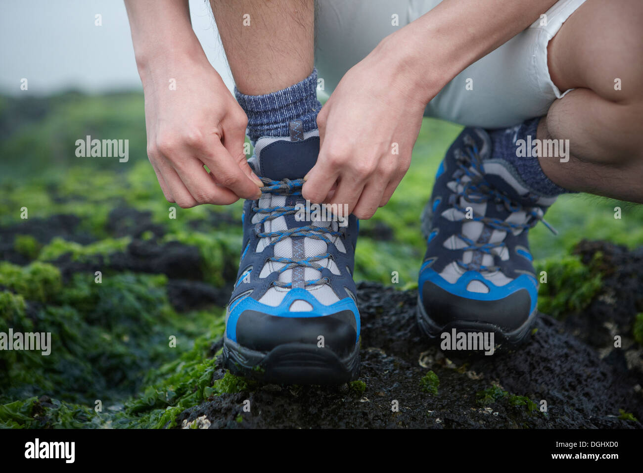 a man tying his shoe laces - Stock Image
