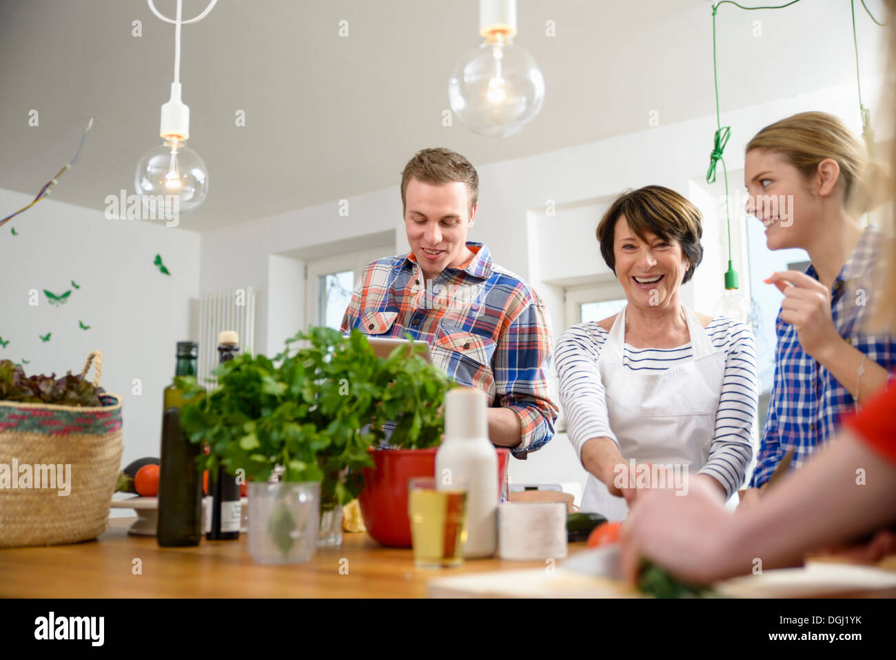 Mother with grown up children preparing food in kitchen - Stock Image