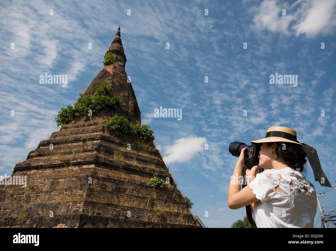 Woman taking photograph at That Dam, Vientiane, Laos - Stock Image