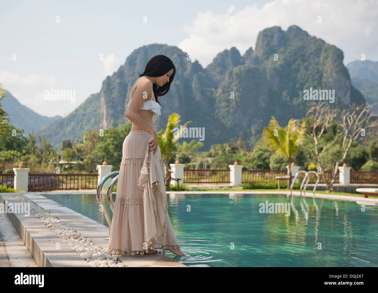 Woman dipping toe in swimming pool, Vang Vieng, Laos - Stock Image