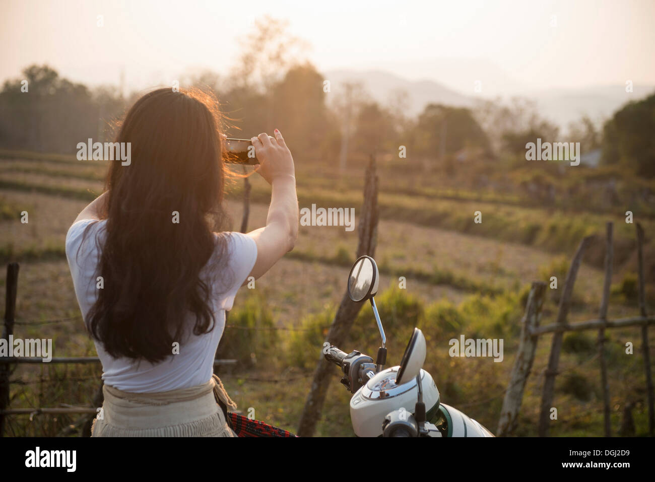Woman on moped taking photograph in rural scene - Stock Image