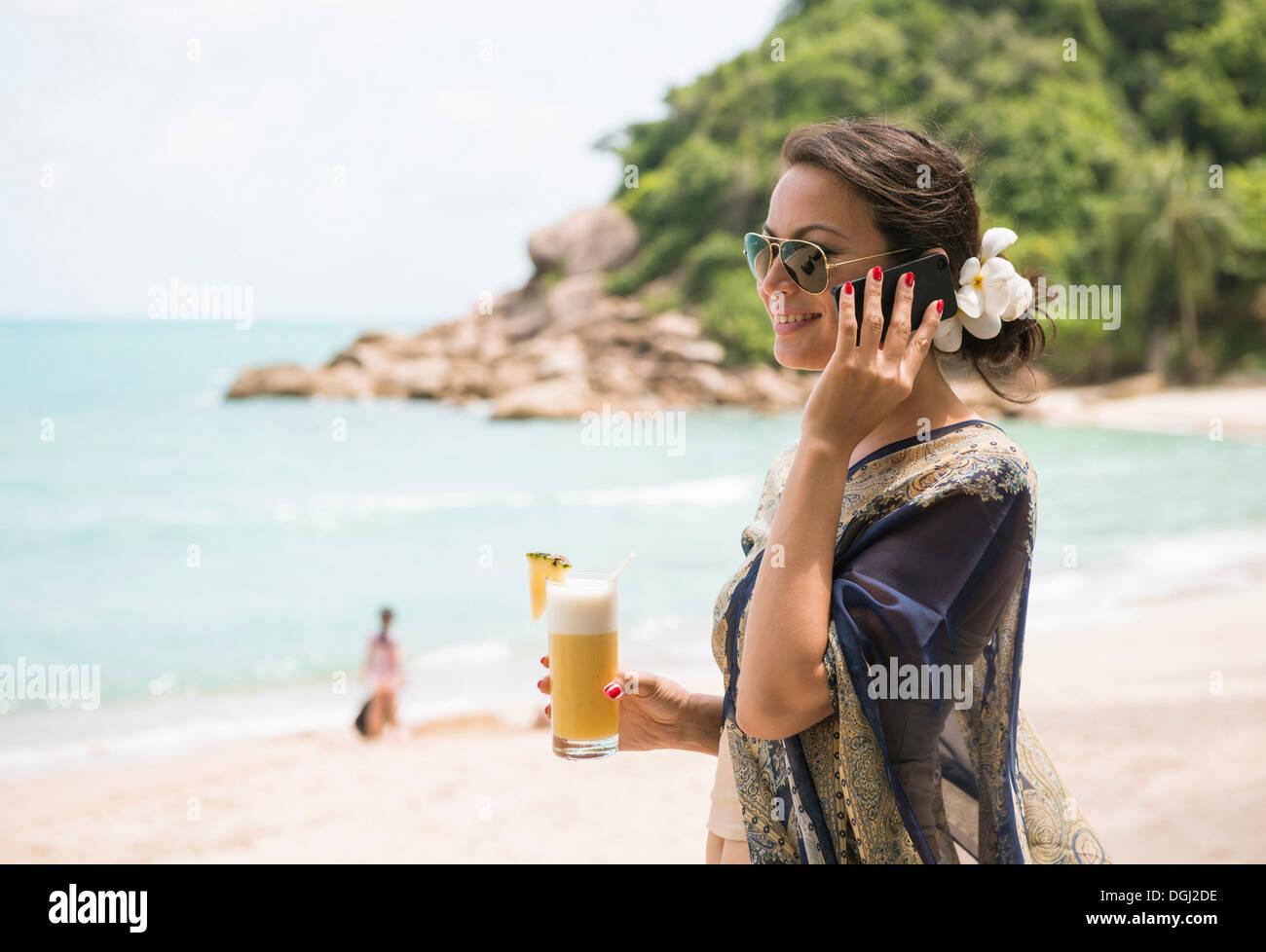 Woman using mobile phone on beach, Banyon Tree Resort, Ko Samui, Thailand - Stock Image