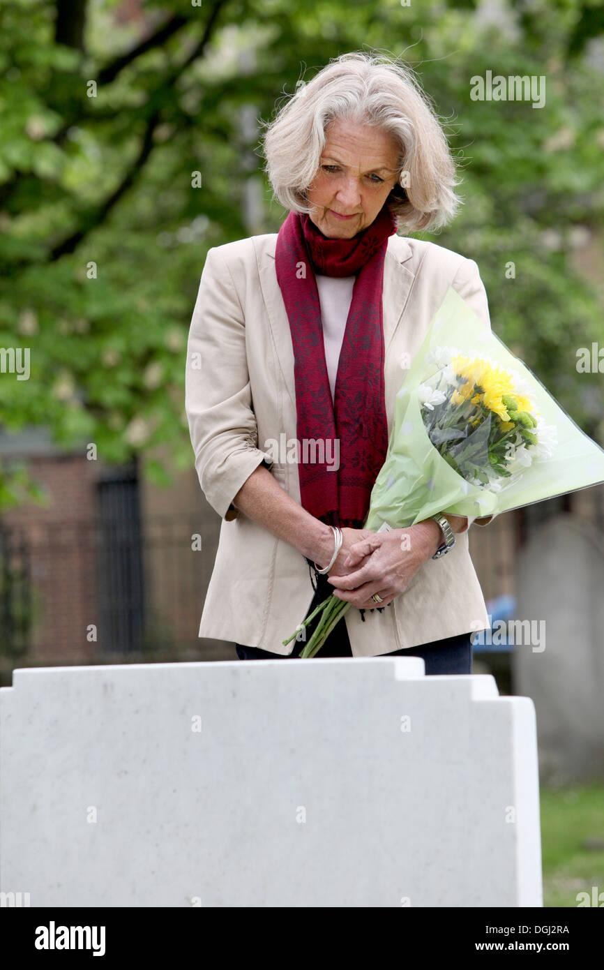 Senior woman holding flowers in graveyard - Stock Image