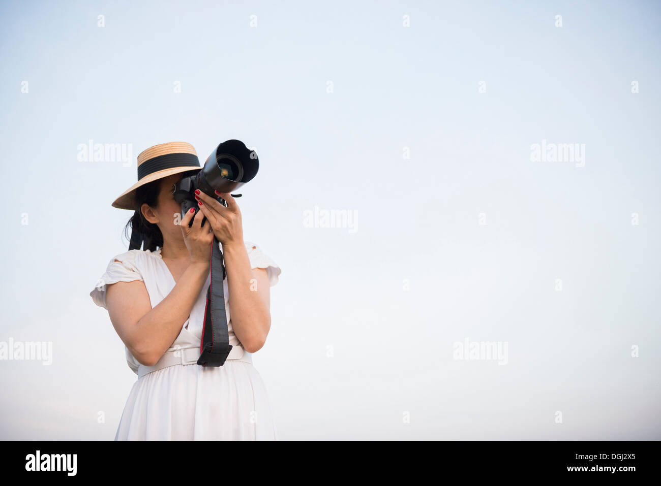 Woman taking photograph against clear sky - Stock Image