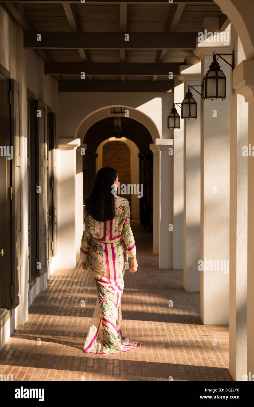 Woman walking past columns in hotel - Stock Image