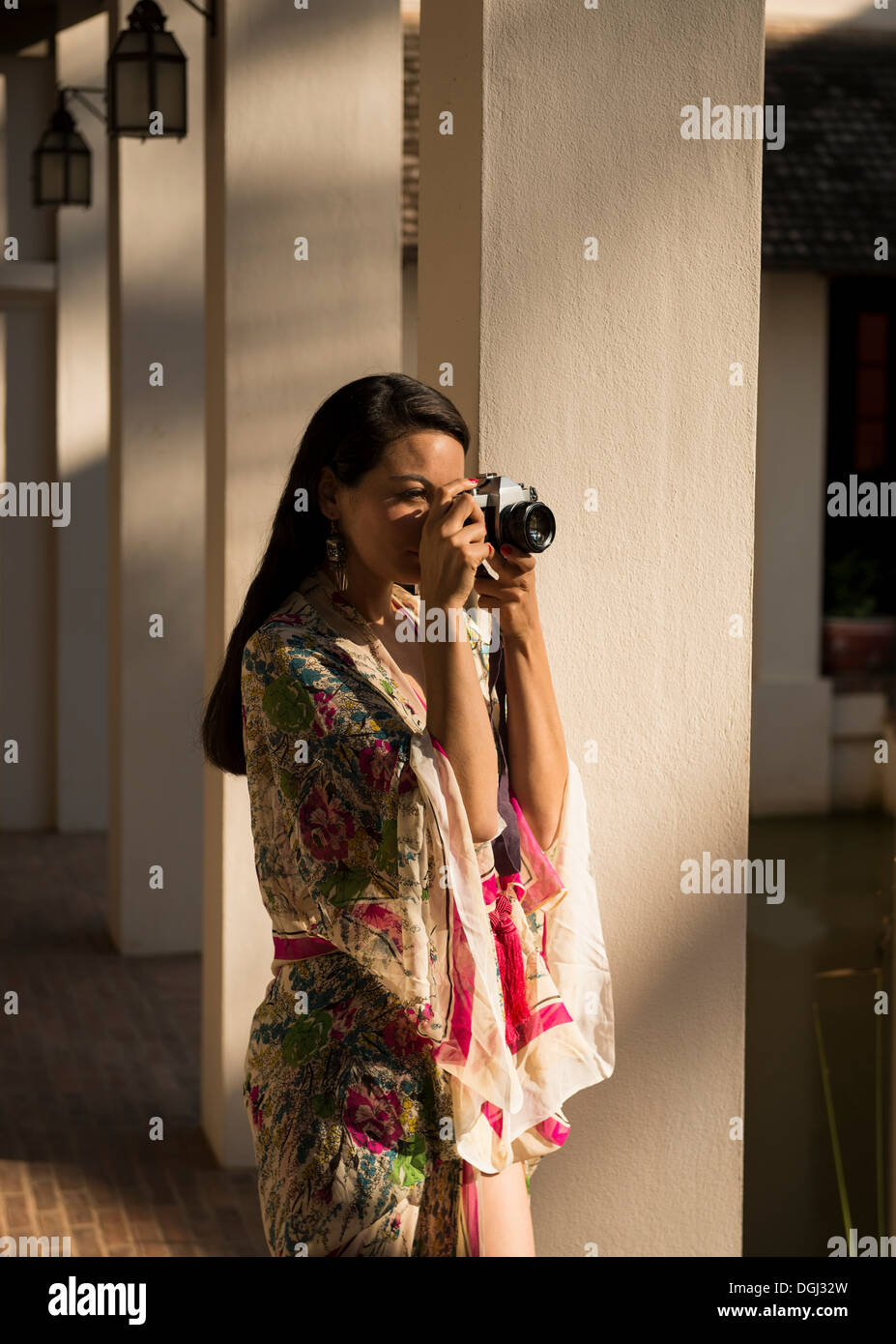 Woman taking photograph by columns in hotel - Stock Image