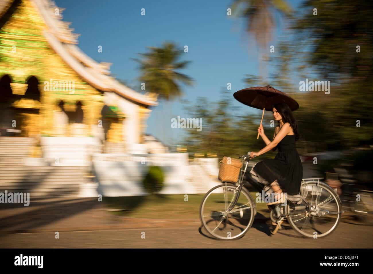 Woman riding bicycle with parasol, Luang Prabang, Laos - Stock Image