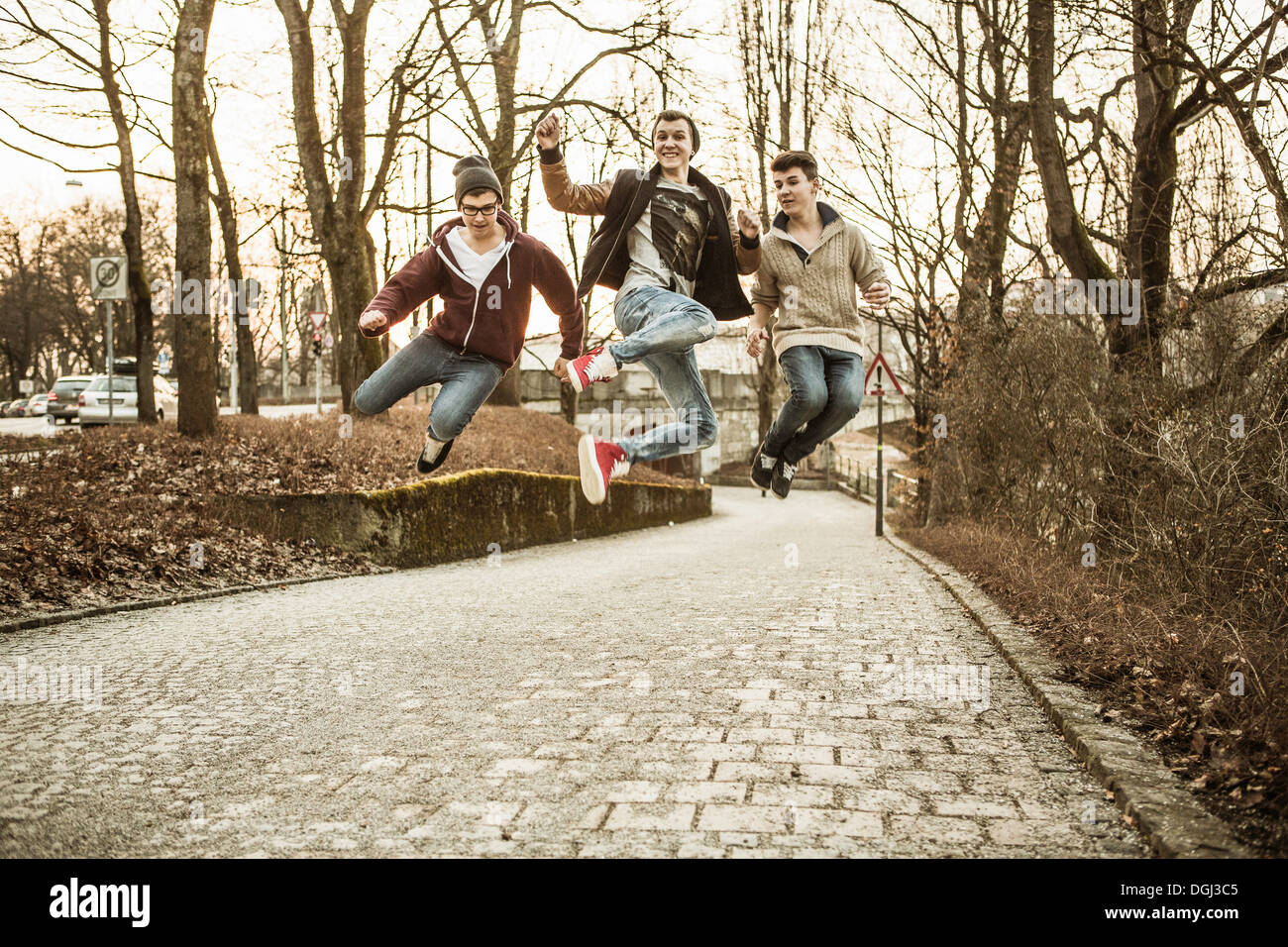 Three teenage boys jumping in park - Stock Image
