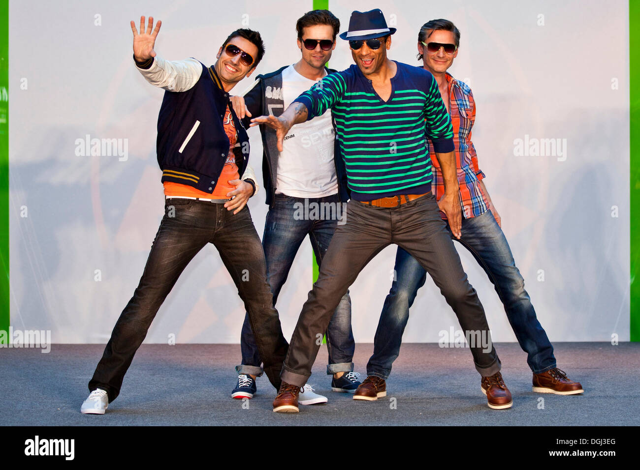 Four male models posing on stage - Stock Image