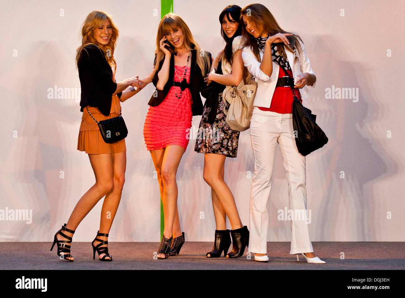 Four female models performing with mobile phones on a stage - Stock Image