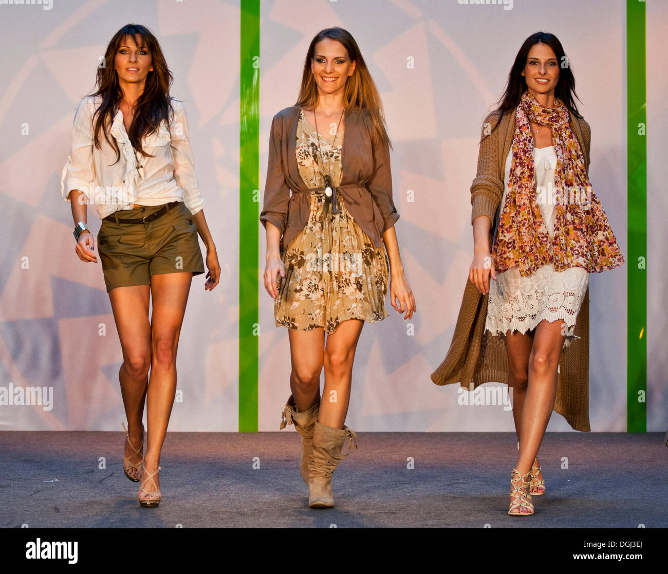 Three models with long hair on a stage - Stock Image