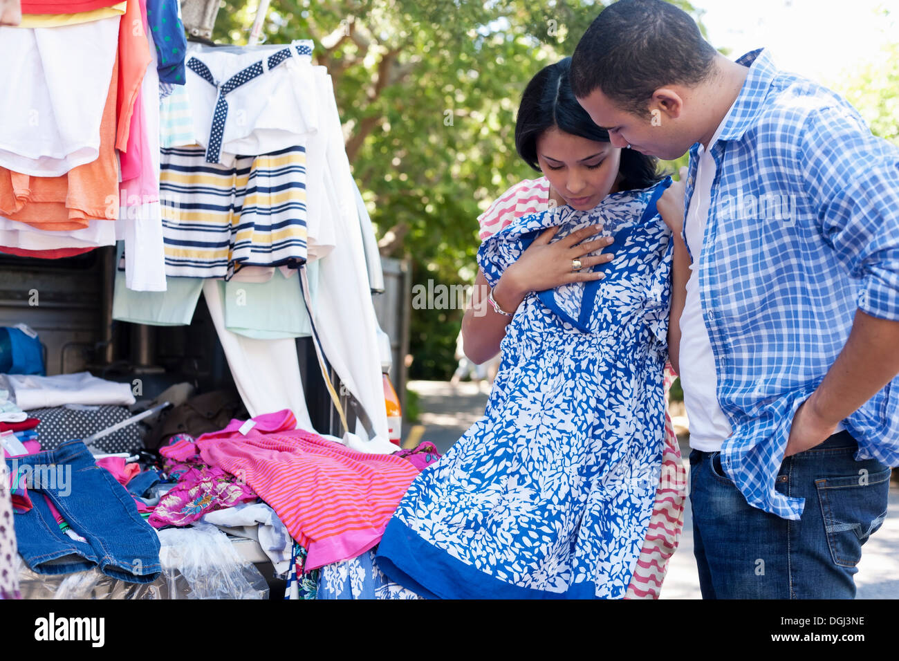 Young woman holding sundress with man watching Stock Photo