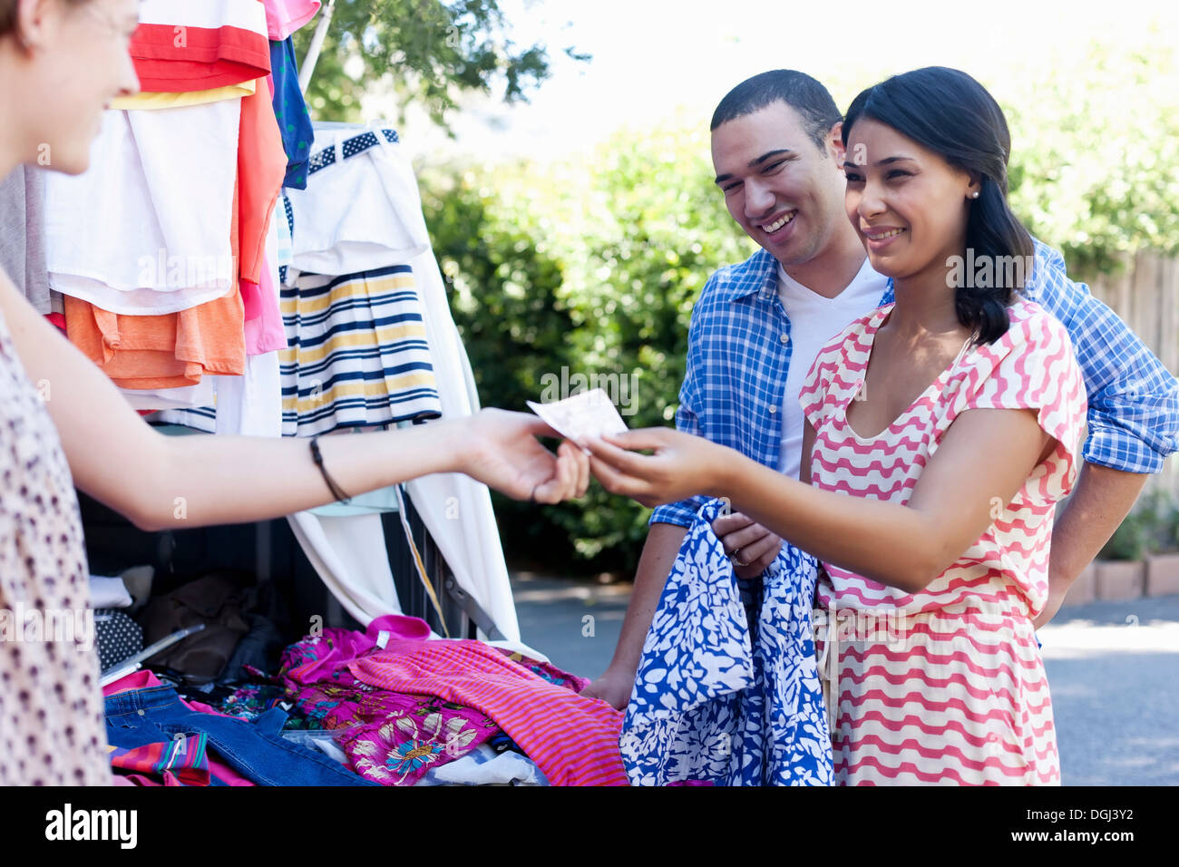 Young woman buying sundress on market stall Stock Photo