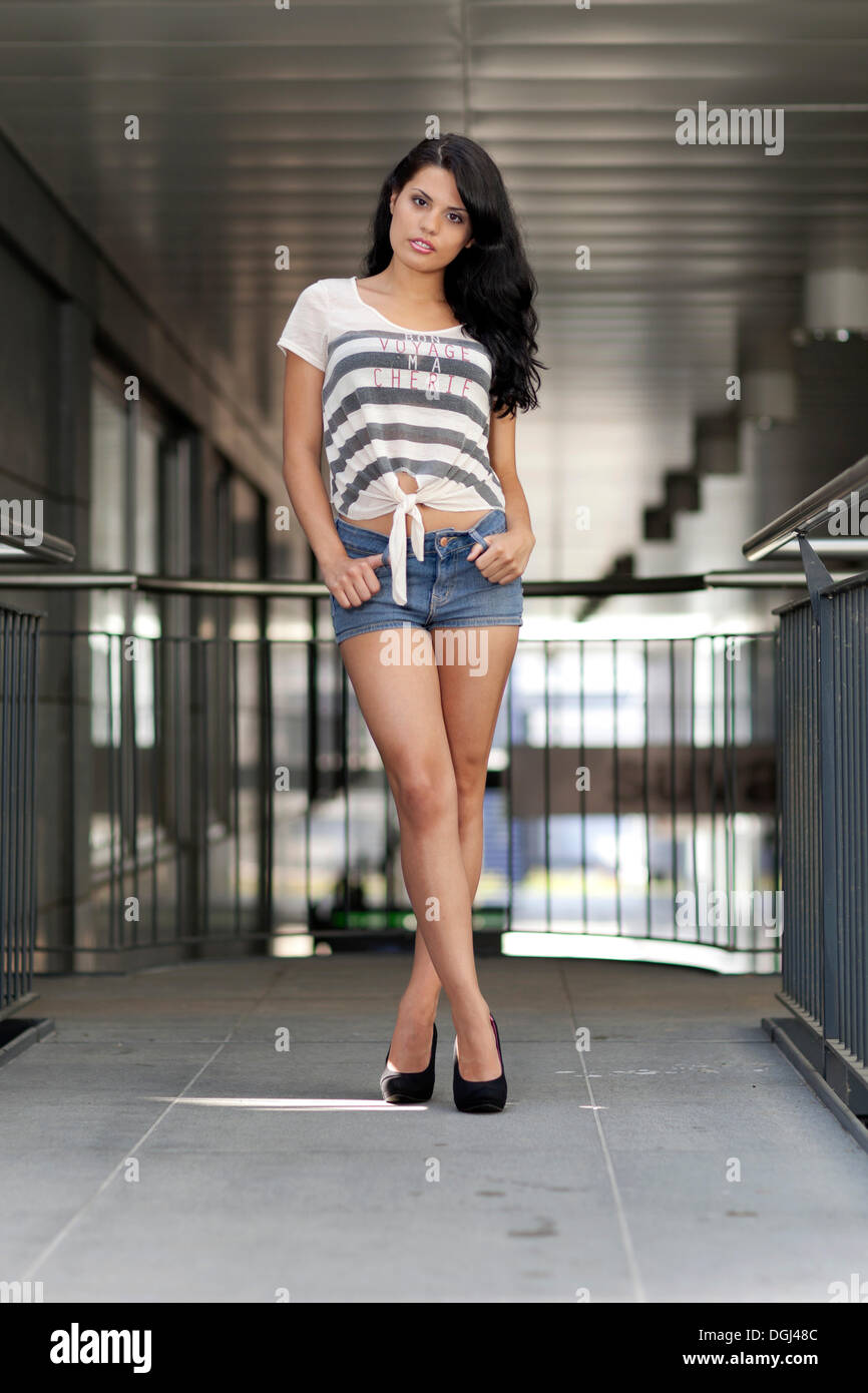 b1cab8dc68c3 Young woman in a stripy T-shirt and denim hot pants and black high heels