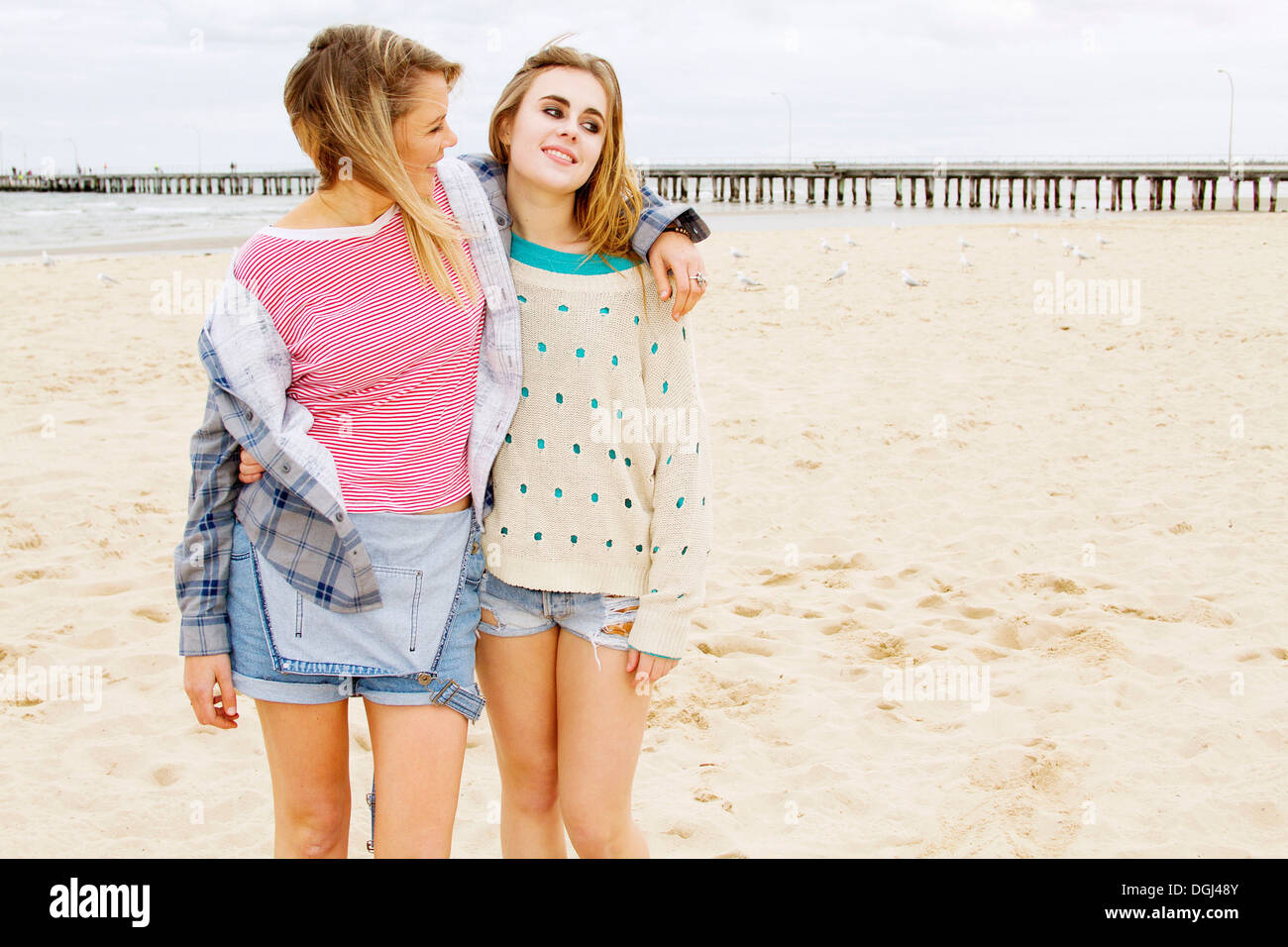 Girlfriends standing on beach with arm around - Stock Image