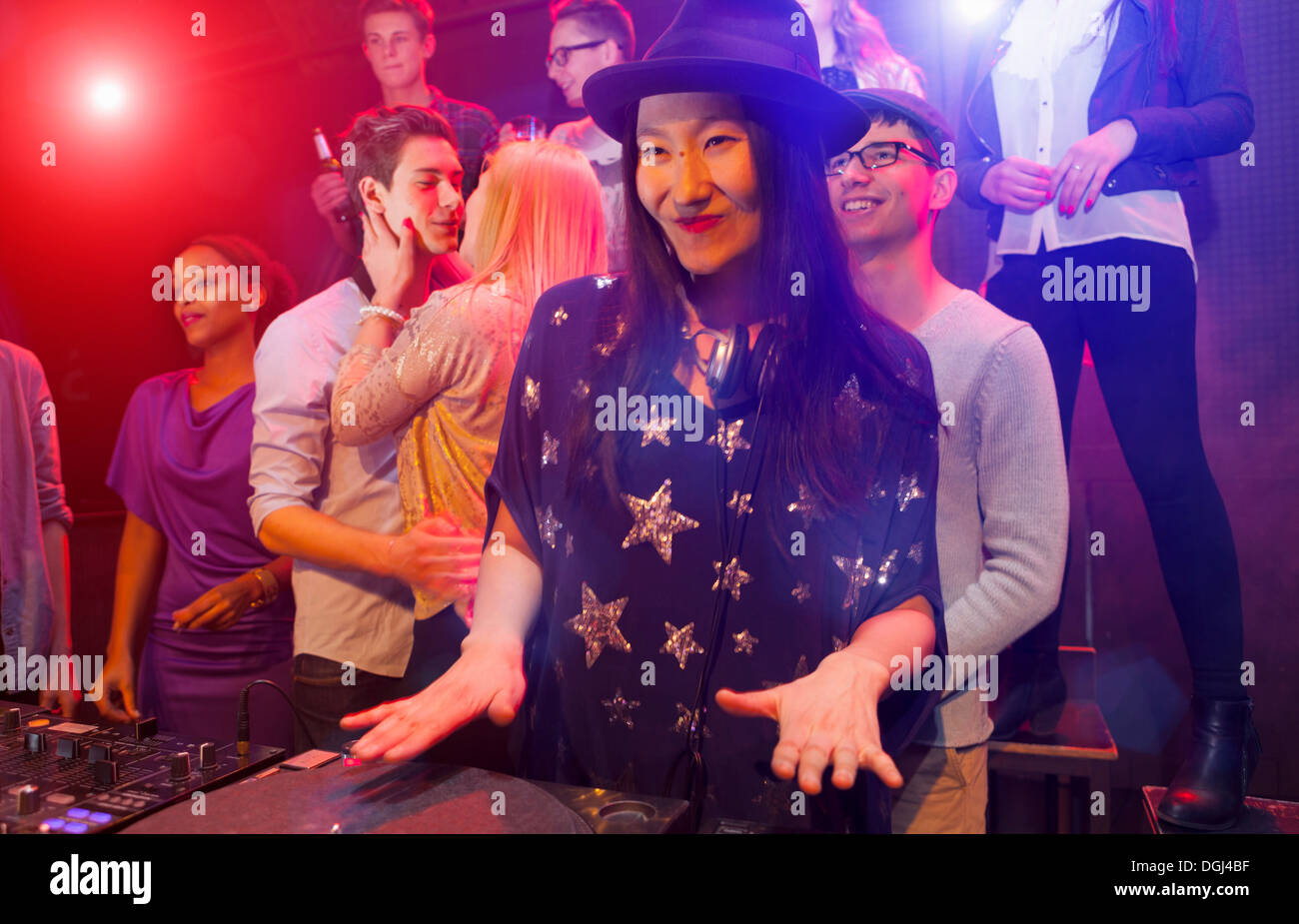 Mid adult woman DJing at party, people dancing in background - Stock Image
