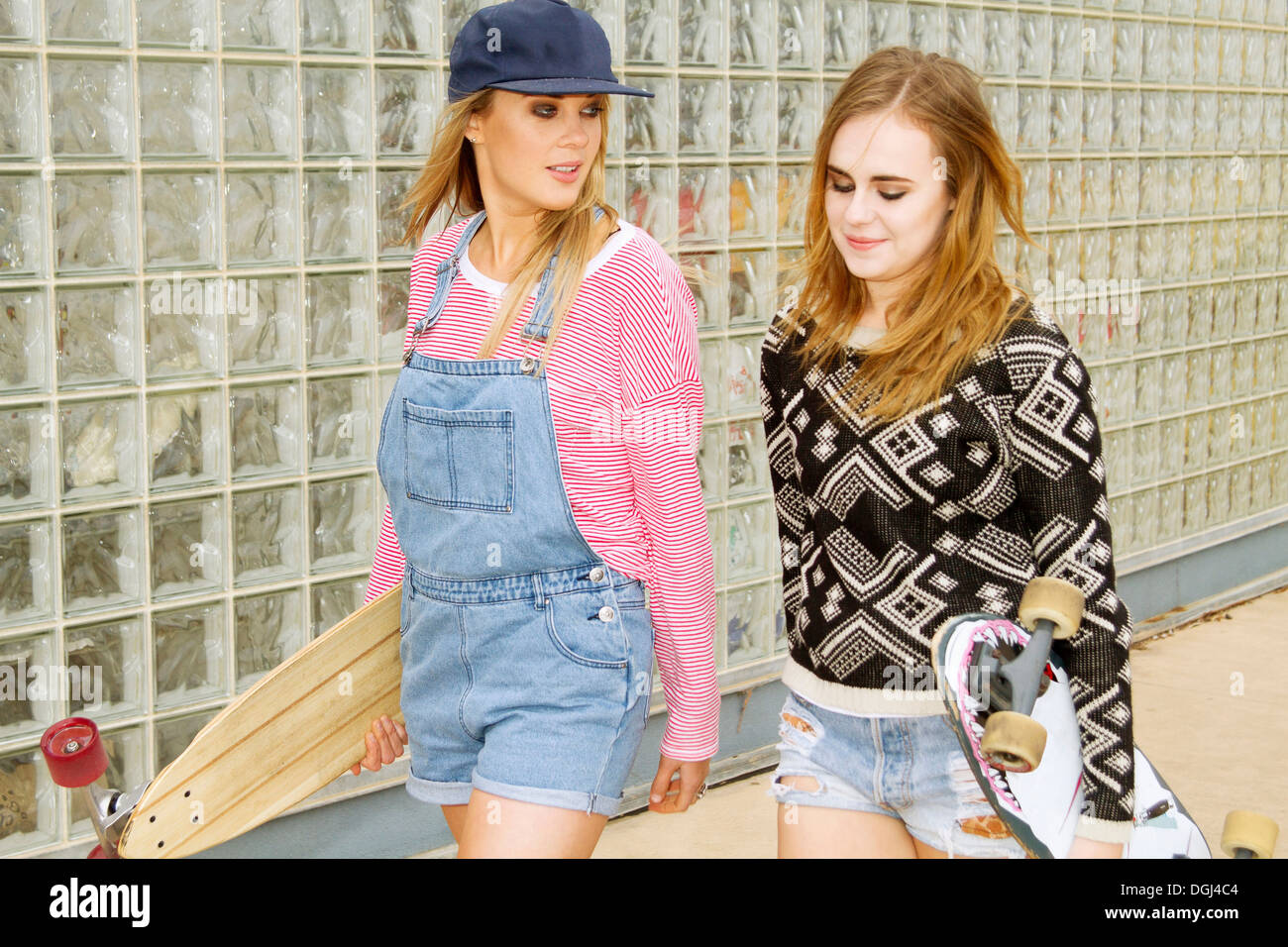 Two young women carrying skateboards beside glass wall - Stock Image