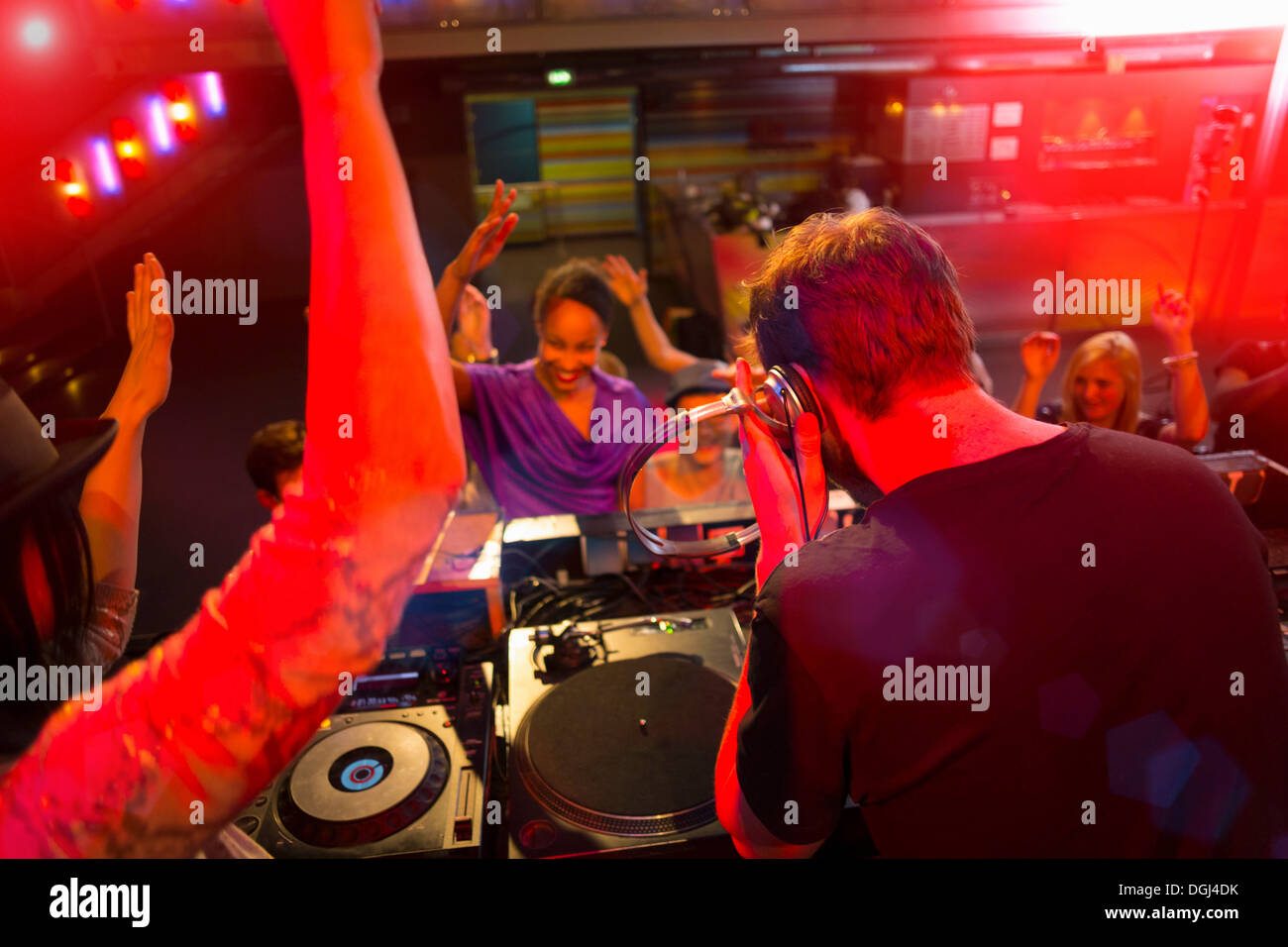 Rear view of disc jockey surrounded by people dancing - Stock Image