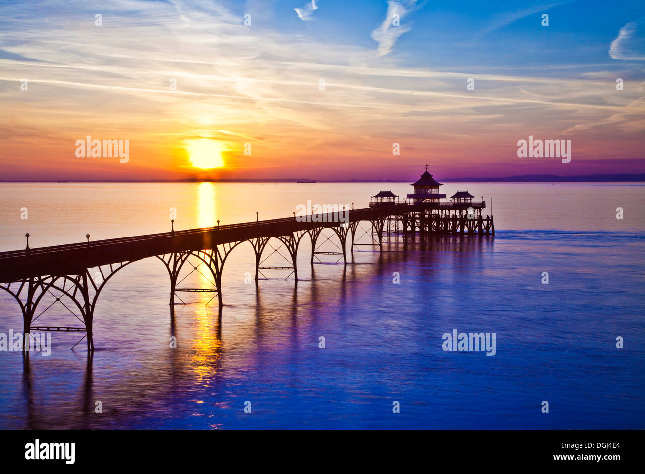 The sun sets over the Bristol Channel behind the pier at Clevedon in Somerset. Stock Photo
